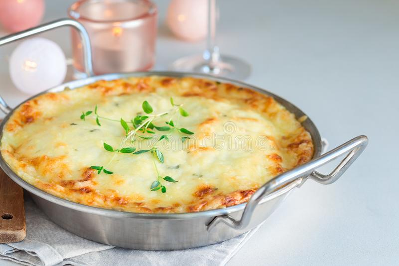 Cheesy scalloped potatoes or potato gratin in baking dish, holiday theme, horizontal, copy space. Cheesy scalloped potatoes or potato gratin in a baking dish royalty free stock photos