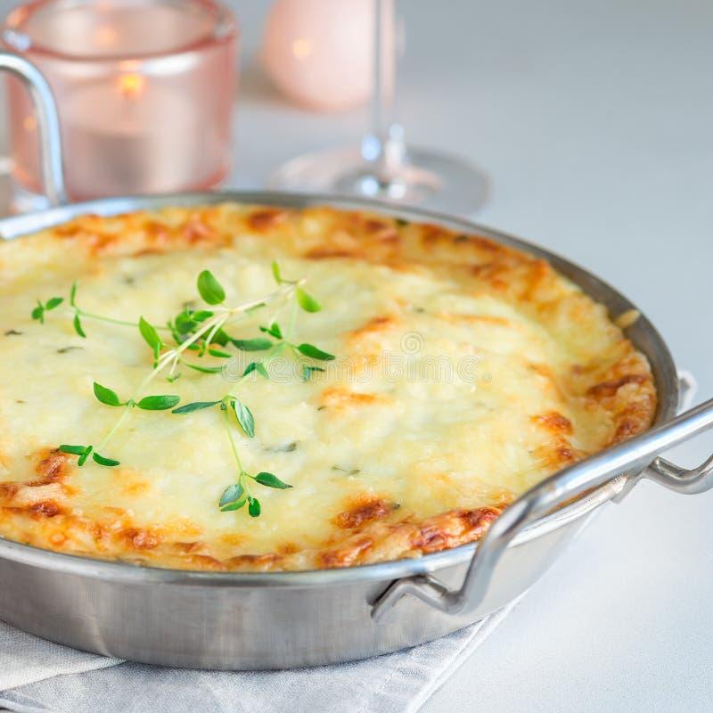 Cheesy scalloped potatoes or potato gratin in baking dish, holiday theme, square format. Cheesy scalloped potatoes or potato gratin in baking dish, holiday theme stock photos