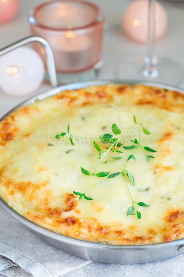 Cheesy scalloped potatoes or potato gratin in baking dish, holiday theme, vertical, closeup. Cheesy scalloped potatoes or potato gratin in a baking dish, holiday stock photo