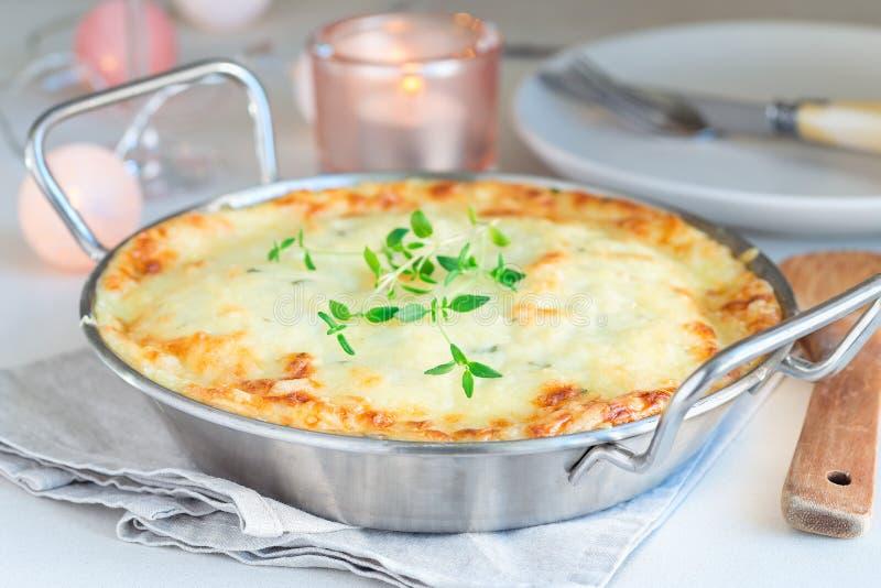 Cheesy scalloped potatoes or potato gratin in baking dish, holiday theme, horizontal. Cheesy scalloped potatoes or potato gratin in a baking dish, holiday theme stock image