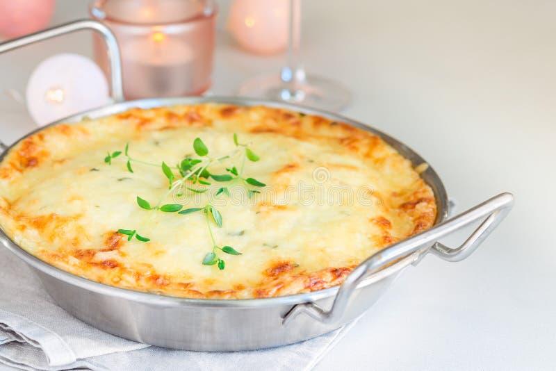 Cheesy scalloped potatoes or potato gratin in baking dish, holiday theme, horizontal, copy space. Cheesy scalloped potatoes or potato gratin in a baking dish stock photography