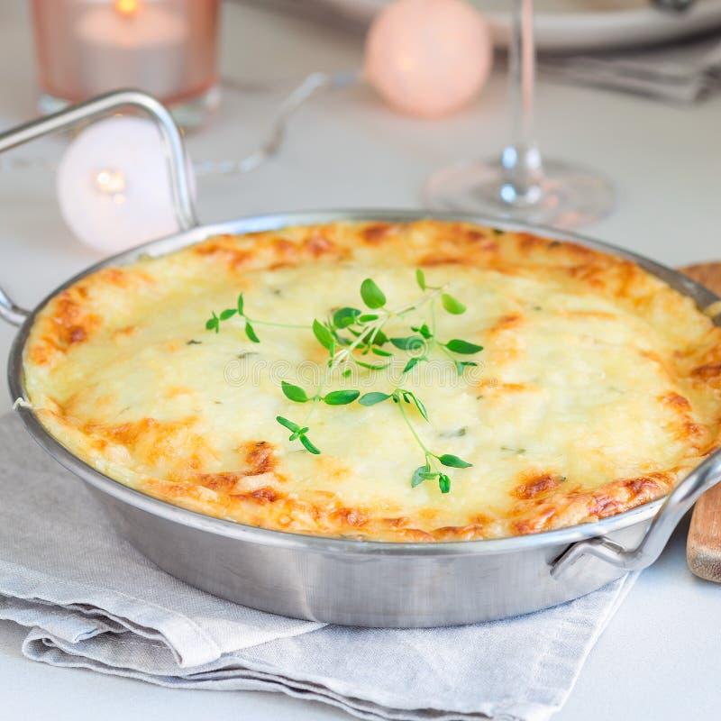 Cheesy scalloped potatoes or potato gratin in baking dish, holiday theme, square format. Cheesy scalloped potatoes or potato gratin in a baking dish, holiday royalty free stock photo