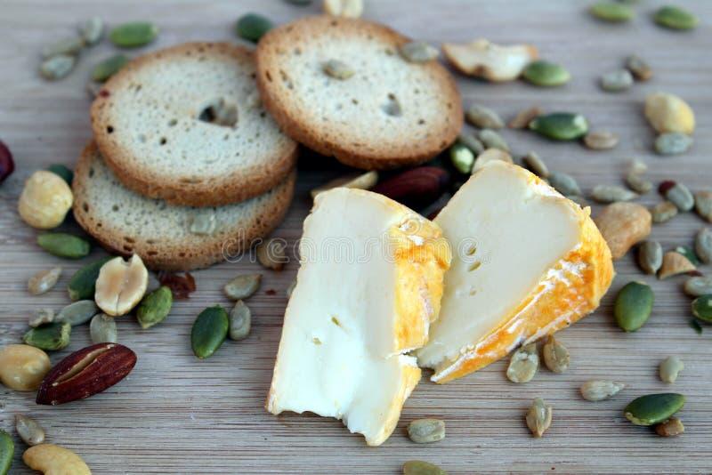 Cheeze快餐用薄脆饼干和混杂的坚果在一个木板 免版税图库摄影