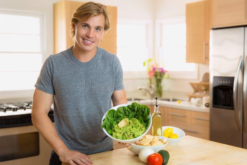 Chef à la maison faisant une portion du guacamole avec un jeune homme avec du charme de sourire dans la cuisine photos libres de droits