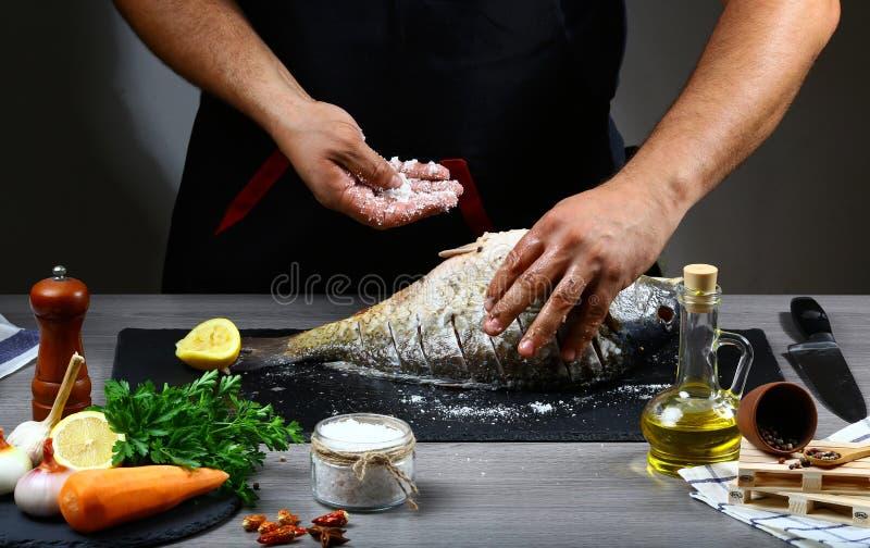 Chef übergibt das Kochen des Fischkarpfens, Zitrone, Kräuter und Gewürze auf einem Schiefer verschalen Chef gießt Olivenöl über f lizenzfreies stockbild