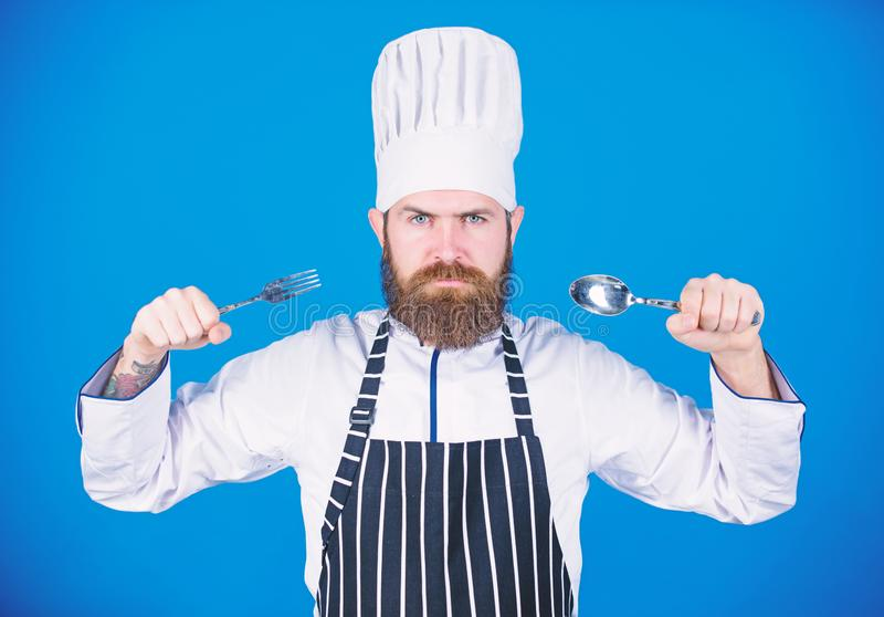 Chef affam? pr?t ? essayer la nourriture Heure d'essayer le go?t Cuill?re et fourchette strictes s?rieuses de prise de visage de  photo libre de droits