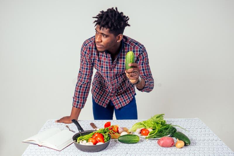 Chef afroamericano mirando el libro de recetas cocinando sabrosas ensaladas cortando verduras en la mesa con fondo blanco foto de archivo libre de regalías
