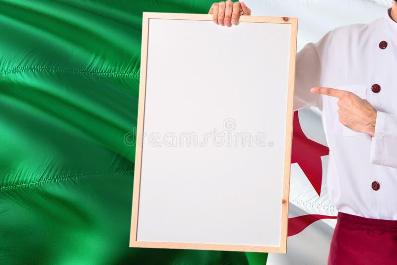 Chef algérien tenant le menu vide de tableau blanc sur le fond de drapeau de l'Algérie Faites cuire l'uniforme de port dirigeant  images libres de droits