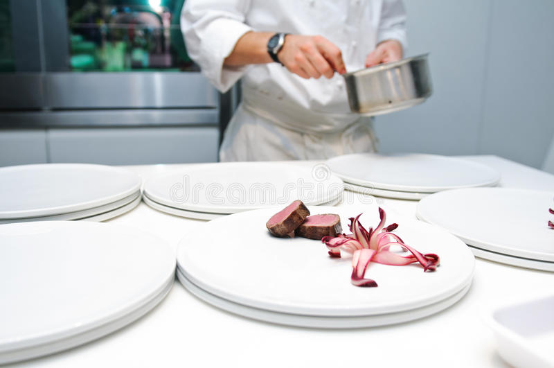 Chef arranging dinner dish. With deer medallion and radicchio royalty free stock photos