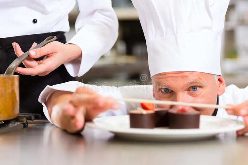 Chef as Patissier cooking in Restaurant dessert stock images