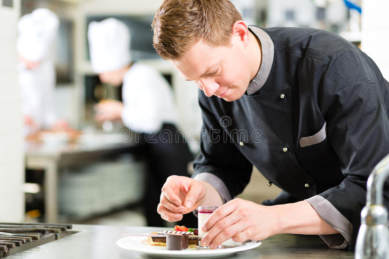 Chef as Patissier cooking in Restaurant dessert. Cook, the pastry chef, in hotel or restaurant kitchen cooking, he is finishing a sweet dessert stock photos