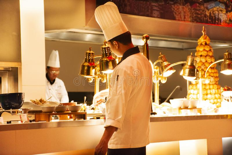 Chef and assistant Chefs cooking and prepared buffet food at restaurant in night time in Bangkok, Thailand stock images