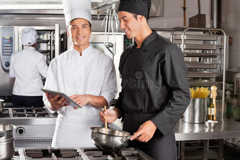 Chef Assisting Colleague In Preparing Food stock images