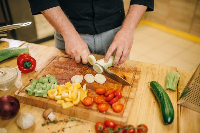 Chef avec des champignons de coupes de couteau sur le conseil en bois photographie stock libre de droits