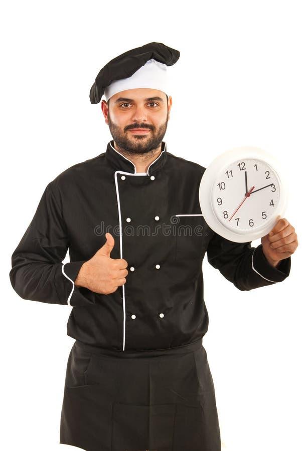 Chef avec l'horloge renonçant au pouce images stock