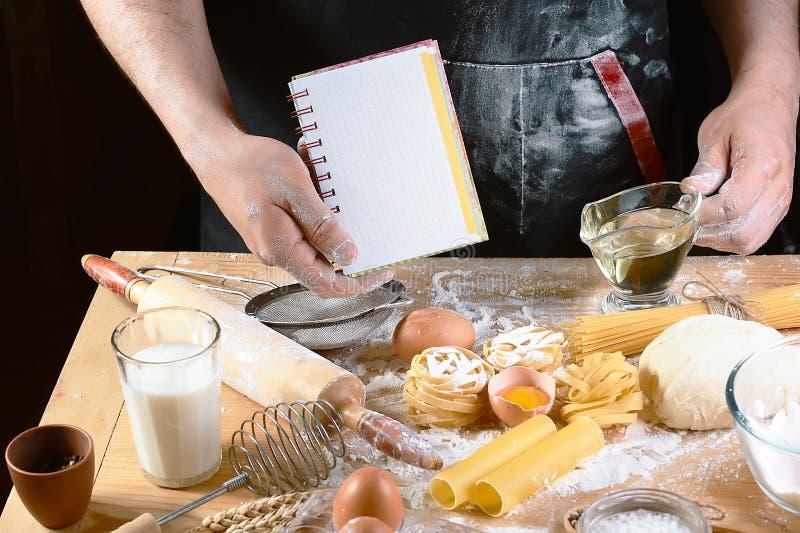 Chef avec le texte de bloc-notes, ngredients pour la pâte, faisant cuire des spaghetti de tagliatelles de pâtes, y compris la far photos libres de droits