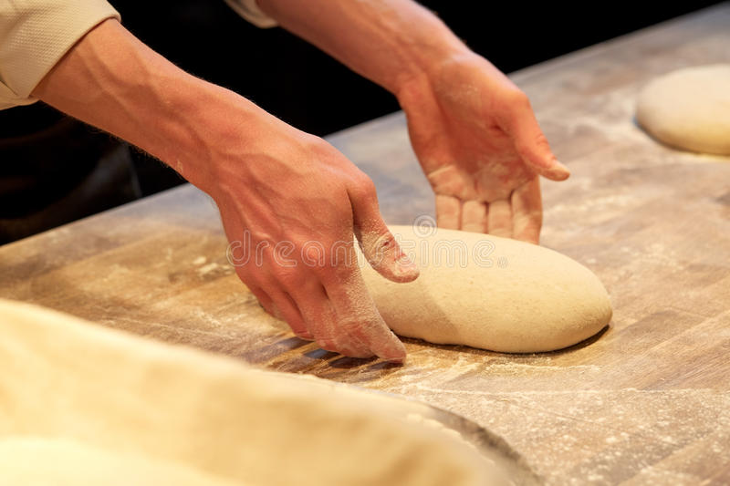 Chef or baker cooking dough at bakery royalty free stock images
