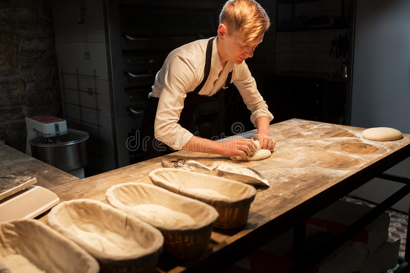 Chef or baker making dough at bakery stock images
