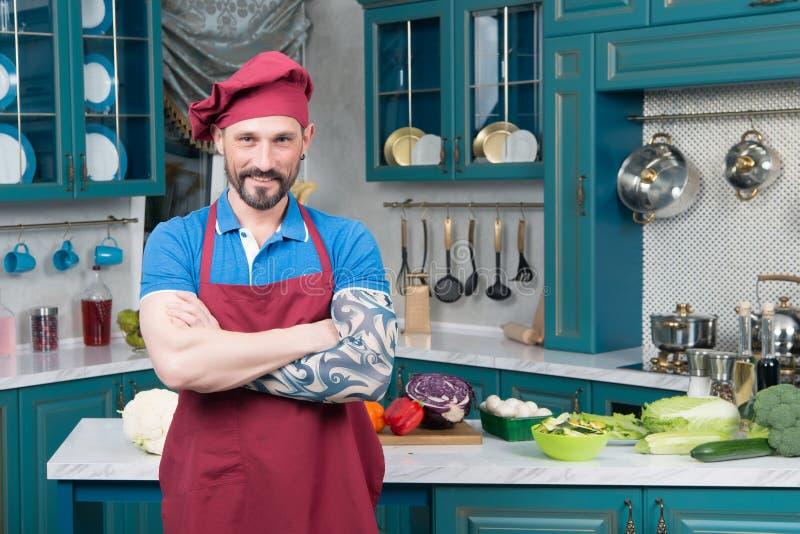 Chef barbu de sourire avec la main tatouée dans le tablier rouge et le chapeau rouge sur la cuisine photos libres de droits