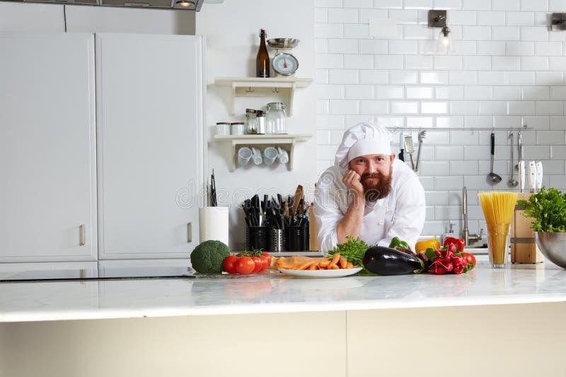 Chef beau dans l'uniforme se tenant sur la cuisine photographie stock libre de droits