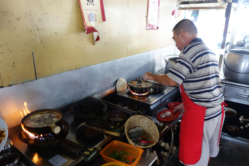 Chef bereitet ein Eintopfgericht von Schweinefleisch und von Kräutersuppe, Ba Kut zu, das in Tanj ist lizenzfreies stockbild