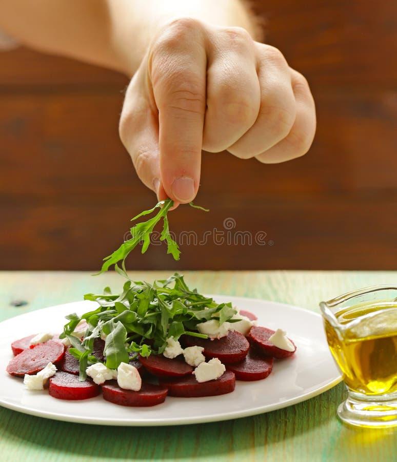 Chef bereitet Salat von gekochten roten Rüben, Käse zu lizenzfreie stockfotos