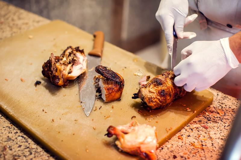 The chef in black apron cuts cooked chicken. The concept of eco-friendly products for cooking stock image