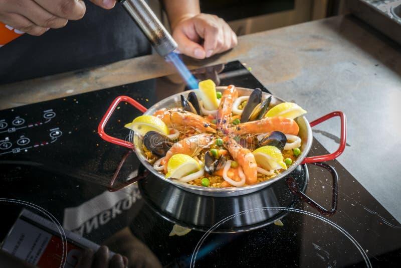Chef brät Meeresfrüchte von Paella mit Brenner lizenzfreies stockbild