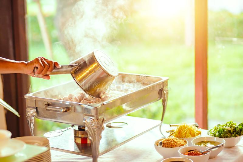 A Chef and breakfast rice gruel in hot tray at the hotel restaurant. Chef and breakfast rice gruel in hot tray at the hotel restaurant stock photo