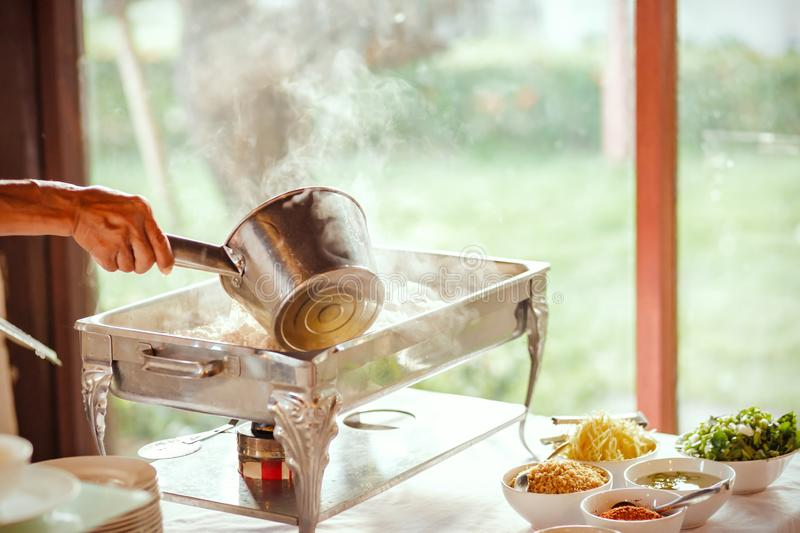 A Chef and breakfast rice gruel in hot tray at the hotel restaurant. Chef and breakfast rice gruel in hot tray at the hotel restaurant royalty free stock image