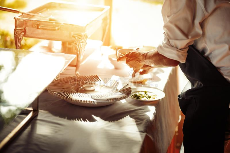 A Chef and breakfast rice gruel in hot tray at the hotel restaurant. dish and spoon are on the table. Chef and breakfast rice gruel in hot tray at the hotel royalty free stock images
