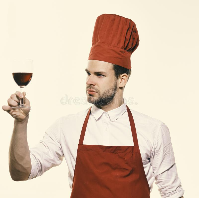 Chef in burgundy uniform with glass of red wine. Cook with satisfied face looks at wineglass. Italian drink concept. Man with beard isolated on white stock photos