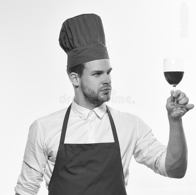 Chef in burgundy uniform with glass of red wine. Cook with satisfied face looks at wineglass. Italian drink concept. Man with beard isolated on white royalty free stock images