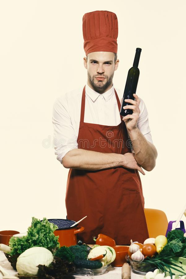 Chef in burgundy uniform holds bottle of wine. Kitchenware and cookery concept. Man with beard isolated on white background. Cook stands by kitchen table with royalty free stock photography
