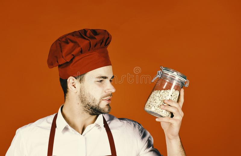 Chef in burgundy uniform holds jar with groats. Breakfast concept. Chef in burgundy uniform holds jar with groats. Breakfast and healthy food concept. Cook with royalty free stock photos