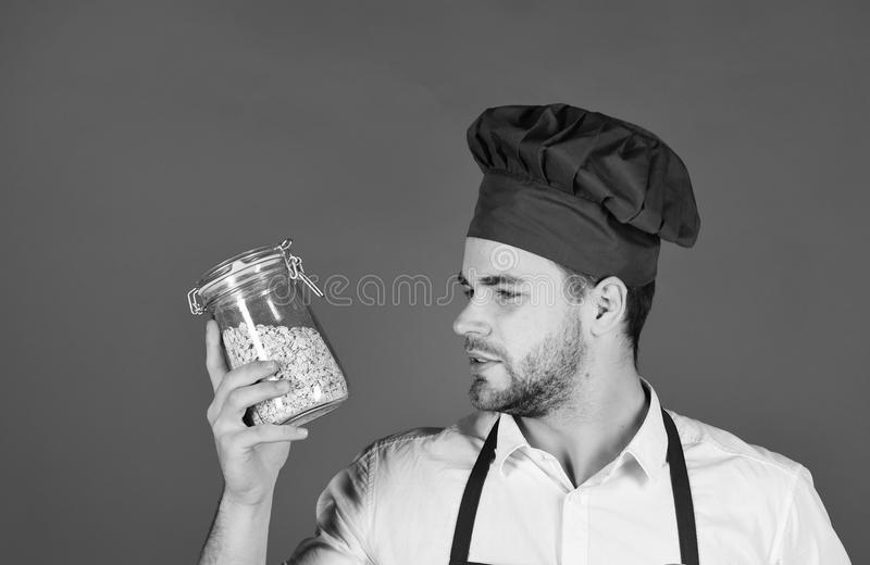 Chef in burgundy uniform holds jar with groats. Breakfast concept. Chef in burgundy uniform holds jar with groats. Breakfast and healthy food concept. Cook with stock image