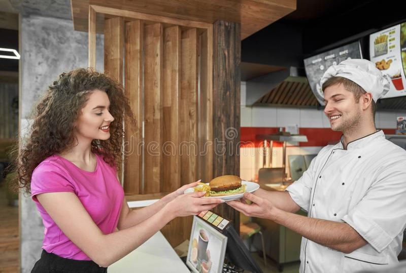 Chef giving girl plate with delicious hamburger. royalty free stock images