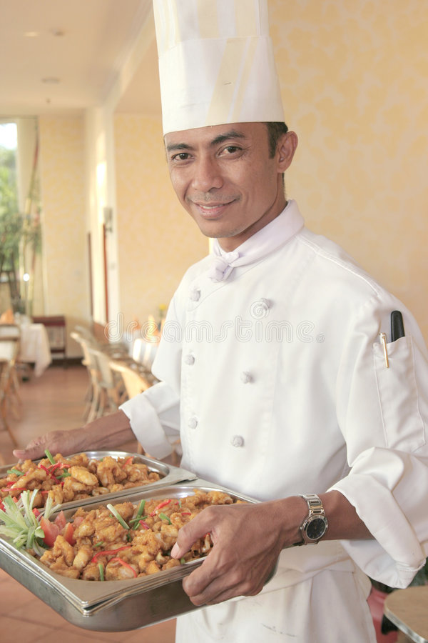 Chef carrying food for buffet. Chef carrying food on chafing dish for buffet royalty free stock image