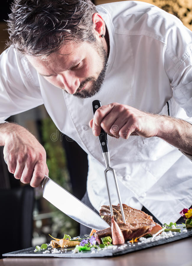 Chef. Chef with knife and fork. Professional chef in a restaurant or hotel prepares or cut up t-bone steak. Chef preparing steak. royalty free stock images
