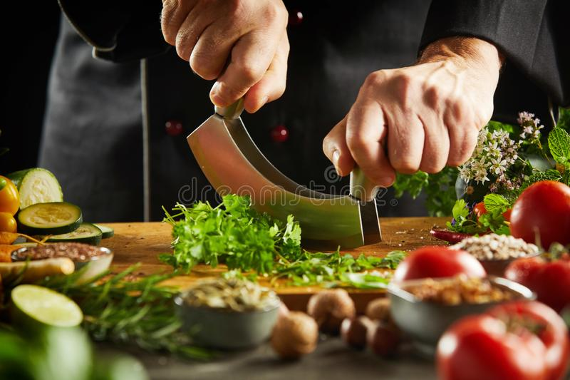 Chef chopping fresh herbs with a mezzaluna knife. On a wooden board in a low angle close up view of his hands stock images