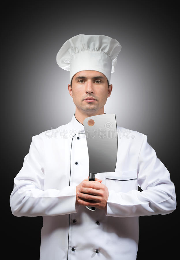 Chef with a cleaver. Portrait of a chef with a cleaver in his hands, studio shot, gray background royalty free stock images