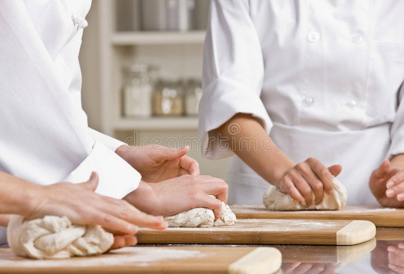 Chef co-workers kneading dough in kitchen stock photography