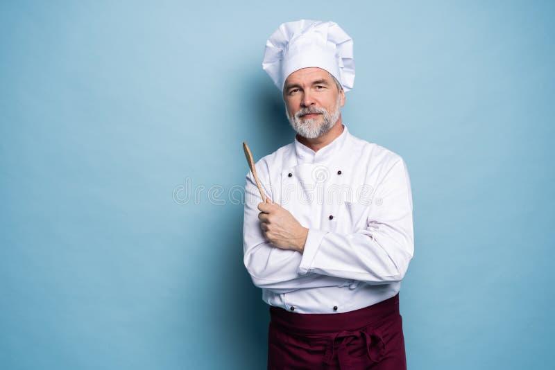 Chef confiant Portrait de chef m?r avec la cuill?re en bois d'isolement sur le bleu image libre de droits