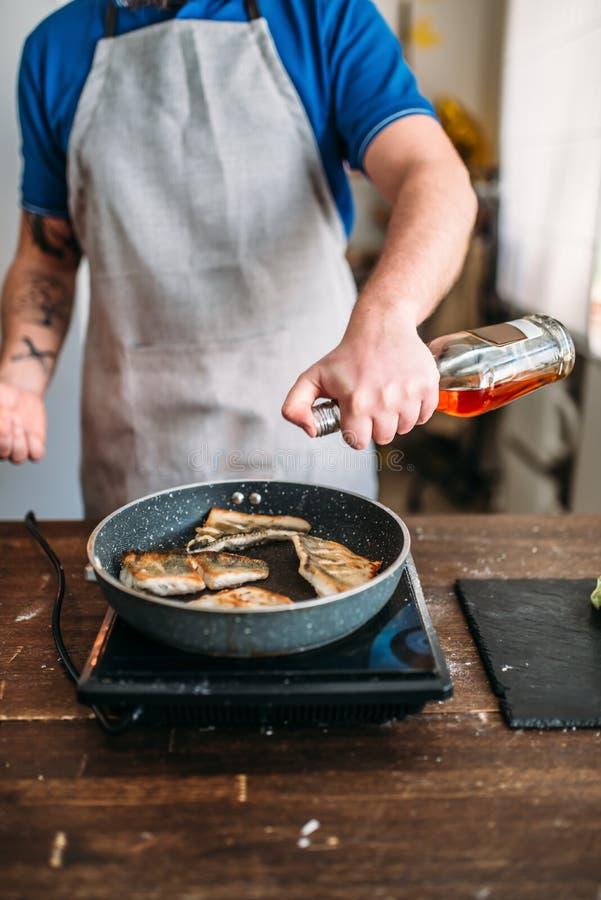 Chef contre la poêle avec le feu, cuisson de poissons photographie stock