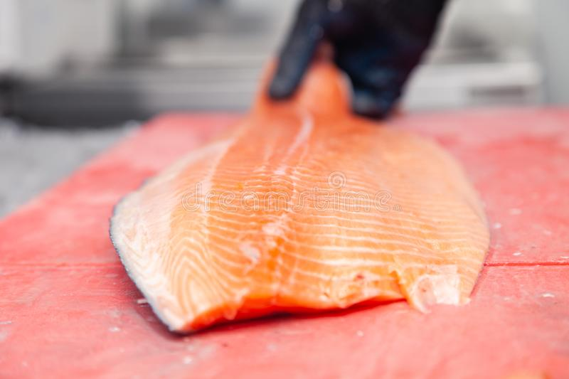 Chef cook carving whole fresh norwegian salmon fish with knife on red cutting board in professional kitchen of restaurant, stock photos