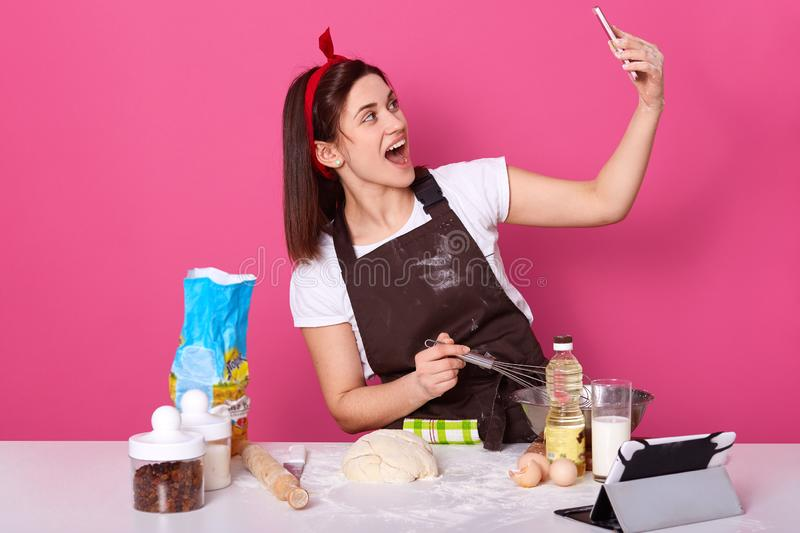 Chef cook confectioner or baker in brown apron, white t-shirt, red hairband, making cake at table, doing selfie on mobile phone, royalty free stock photo