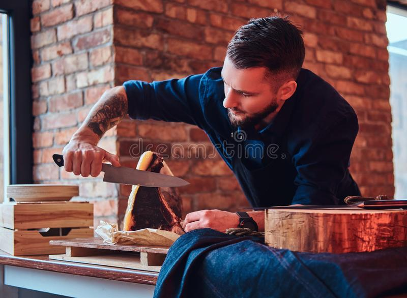 Chef cook cutting exclusive jerky meat on table in a kitchen with loft interior. royalty free stock photos