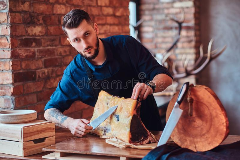 Chef cook cutting exclusive jerky meat on table in a kitchen with loft interior. stock photos