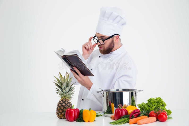 Chef cook in glasses reading recipe book. Portrait of a male chef cook in glasses reading recipe book isolated on a white background stock photos