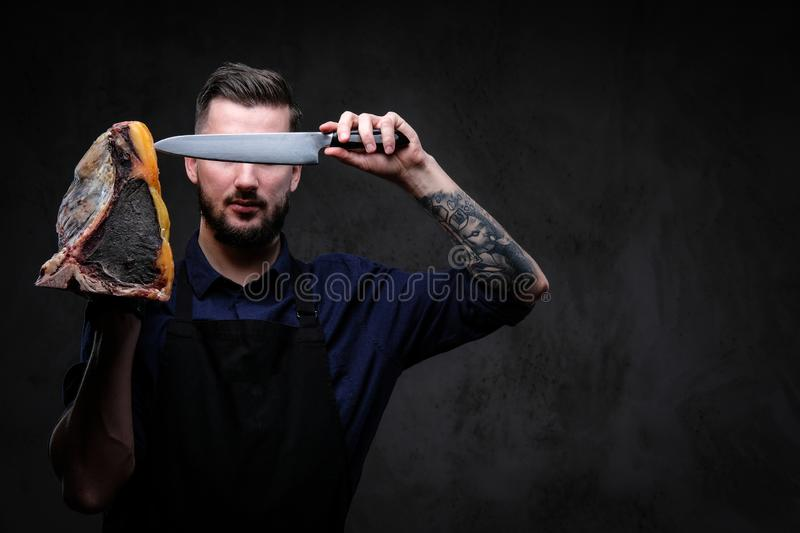 Chef cook holds the knife and large piece of exclusive cured meat on a dark background. stock photography